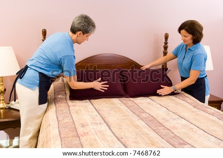 Two maids work as a team fluffing pillows after making the bed.