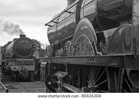 Two mainline steam trains facing each other across an old style turntable. Old steam.