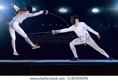 Two male and female fencing athletes fighting on professional sports arena