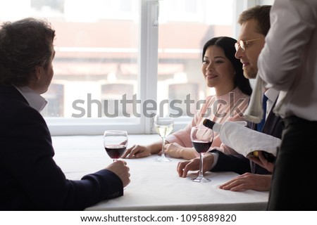 Two male and one female partners having wine before business lunch at luxury restaurant. #1095889820