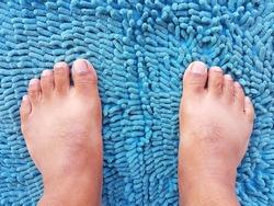 two male asian feet on blue scraper