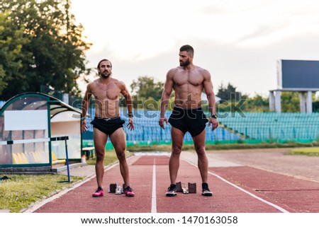 Two male athletes getting ready for running on a track