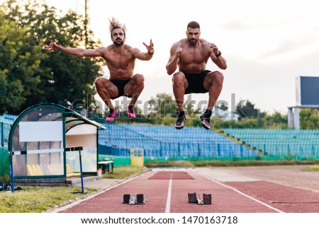 Two male athletes warming up for running on a track