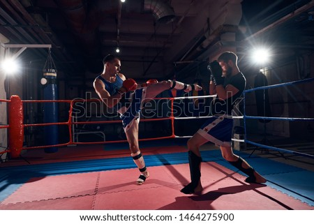 Two male attractive sportsmen kickboxers fighting in the ring at the sport club