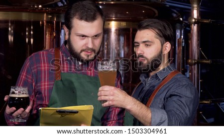 Two male brewers examining delicious craft beer they manufacture together