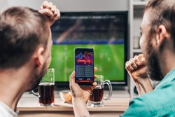 Two male buddies watching live football game broadcast on tv and celebrating money win after making bets online at bookmakers website.