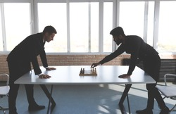 two male businessmen, rivals are playing chess. Strategy and rivalry.