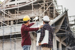 Two male engineer looking commercial building structure, blur image