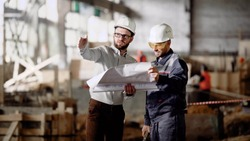 Two male engineers are standing in the building site and holding construction plan. Businessmen dressed in white protective hardhats working together and discussing detailes of design project.