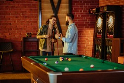Two male friends playing snooker and having fun together in a pub