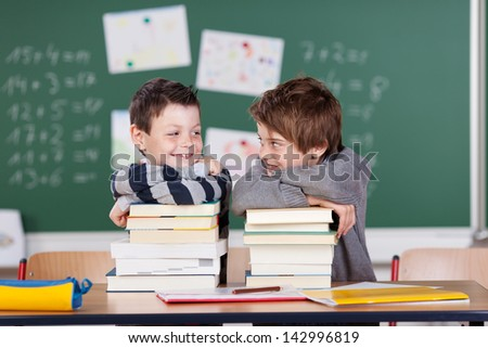 Two male friends studying with a pile of books on the table