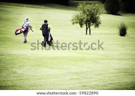 Two male golf player walking on fairway with their golf bags, plenty of copy-space.