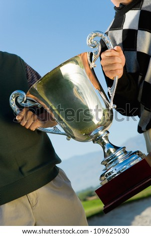 Two male golfers holding trophy on golf course