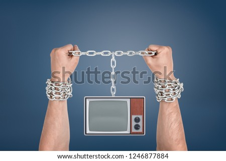 Two male hands bound together with metal chains and linked to a retro TV unit with blank screen. Bound by media. Information slaves. TV addiction.