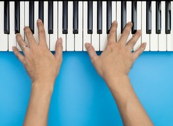 Two male hands playing on music keyboard on blue background