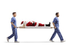 Two male health workers carrying Santa Claus on a stretcher  isolated on white background