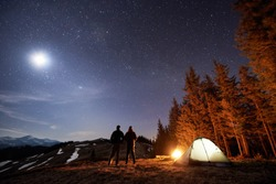 Two male hikers have a rest in his camp near the forest at night. Men standing near campfire and tent under beautiful night sky full of stars and the moon, and enjoying night scene