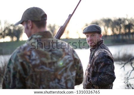 Two male hunters wearing camouflage clothing