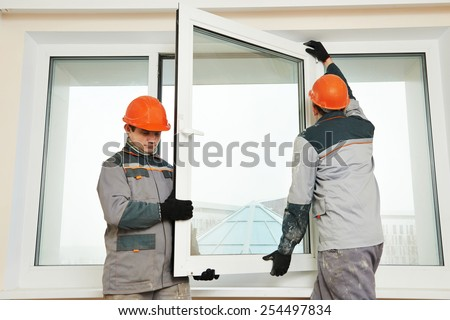 Two male industrial builders workers at window installation stock photo