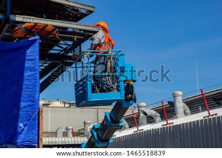 Two male industry working at high in a boom lift electrical wiring system