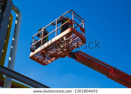 Two male  industry working at high in a boom lift  inspection of pipeline oil