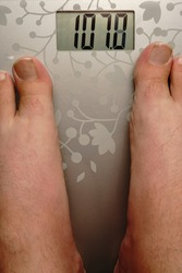 Two male legs stand on the scales. The weight is almost more than one hundred and ten kilograms.