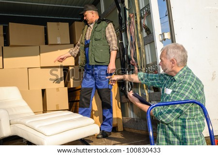Two male movers unload furniture and boxes  from moving truck