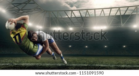 Two male Rugby players fight for the ball in flight on professional rugby stadium