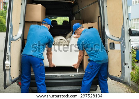 Two Male Workers In Blue Uniform Adjusting Sofa In Truck