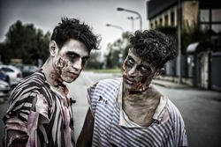 Two male zombies standing in empty city street looking at camera