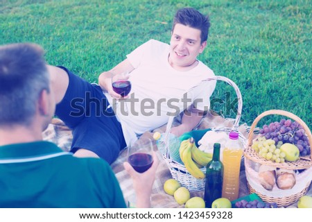 Two males enjoying life on picnic outdoors in male company