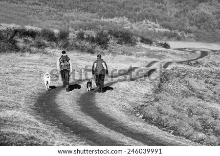 two man and dog walk on dirt road in sunset time, black and white landscape