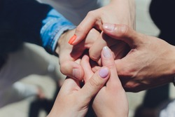 two man and three women holding hands on a table implying a polyamory relationship or love triangle.