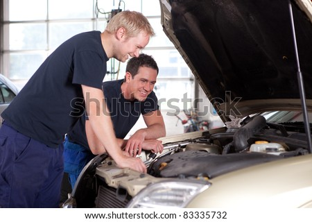 two man mechanics smiling and working under the hood of a car shallow depth of field sharp. Black Bedroom Furniture Sets. Home Design Ideas