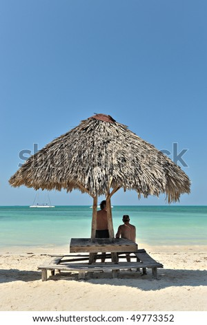 Two man relaxing on beautiful tropical beach