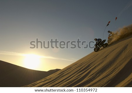 Two man riding quad bike in desert at sunset