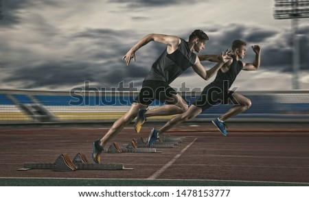 Two man sprinter leaving starting blocks on the athletic track