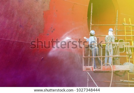 two man worker cleaning cargo ship side of ship and boat propeller with scaffolding at shipyard