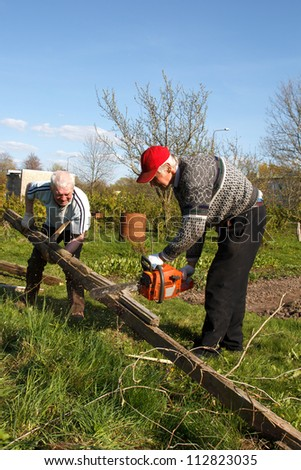 two man working in garden. destroy old building and sawing planks.