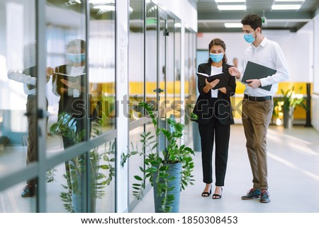Two manager in protective face masks having an argument discussing business Issue. Holds a folder with important documents in his hands. Covid-19. Photo stock ©