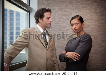 Two managers standing at a window in corporate building
