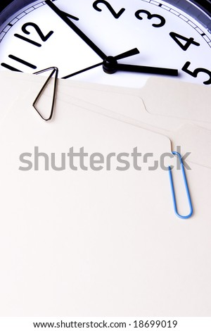 Two manila file folders with paperclips laying on a clock face.  The clock reads a little after five o\'clock.