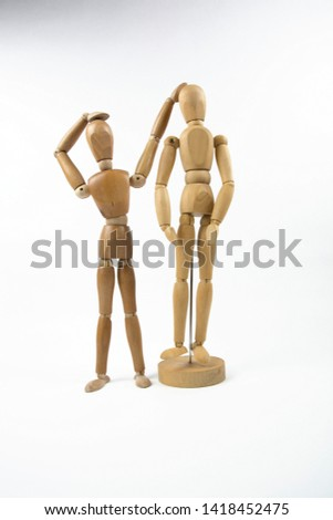 Two mannequins stand isolated against a white background. the shorter mannequin is measuring his own height against the taller mannequin.