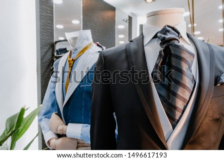 Two mannequins wearing a suit and tie