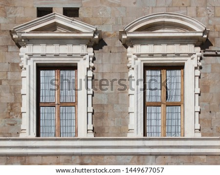 Two mannerist windows topped by a pediment at Palazzo alla Giornata in Pisa, Italy