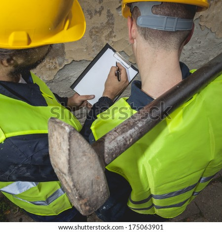 Two manual hard workers on field writing down the water inside of manhole at the road. Detail, view from above.