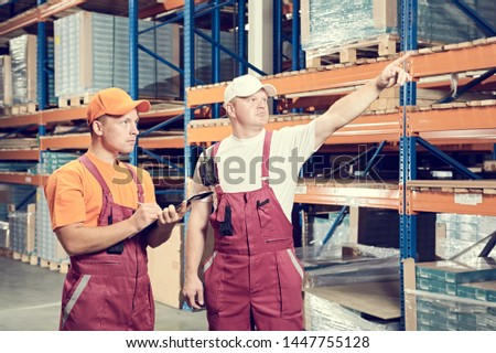 two manual workers in warehouse in front of racks