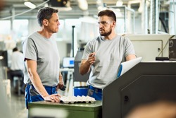 Two manual workers talking while working in a industrial facility.
