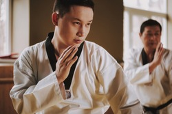 Two martial arts students in white keikogi with black belts training doing karate stances. Chinese man in white kimono takes up a defense stand