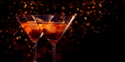 Two martini glasses in front of red bokeh background. Luxury cocktail drink in restaurant bar with night lights blur. Classy beverage celebration party for new year, christmas, valentine.